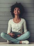 Девушка Афро американская с устройством стоковые изображения