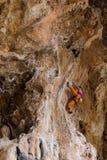 Девушка альпиниста утеса в оранжевых брюках Стоковые Фотографии RF