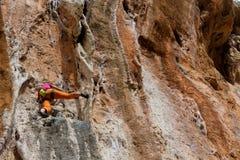 Девушка альпиниста утеса в оранжевых брюках Стоковое Изображение RF