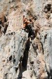 Девушка альпиниста утеса в оранжевых брюках Стоковая Фотография