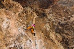 Девушка альпиниста утеса в оранжевых брюках Стоковое Фото
