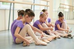 Девушка балета регулируя ее ботинки балета Стоковая Фотография