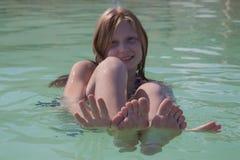 Девушка балансируя на воде в мертвом море Стоковое Изображение