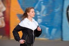 Девушка бегуна на jogging практике около стены граффити Стоковое Изображение RF