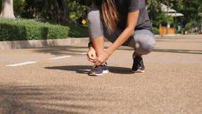 Девушка бегуна смешанной гонки Active подходящая молодая связывая шнурки ботинка в парке 4K bangkok Таиланд акции видеоматериалы