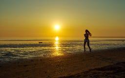 Девушка бежать морем на пляже Стоковая Фотография RF