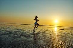 Девушка бежать морем на пляже Стоковые Фотографии RF