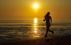 Девушка бежать морем на пляже Стоковое фото RF