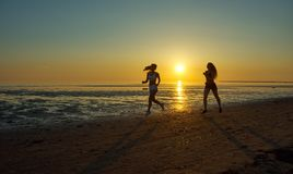 Девушка 2 бежать морем на пляже Стоковая Фотография RF