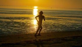 Девушка бежать морем на пляже Стоковые Фото