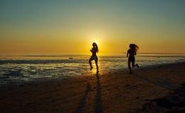 Девушка 2 бежать морем на пляже Стоковое фото RF