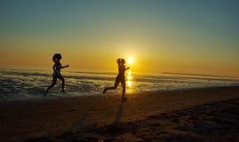 Девушка 2 бежать морем на пляже Стоковые Изображения
