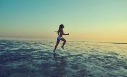 Девушка бежать морем на пляже Стоковые Изображения RF