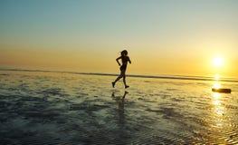 Девушка бежать морем на пляже Стоковая Фотография
