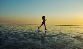 Девушка бежать морем на пляже Стоковые Изображения