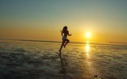 Девушка бежать морем на пляже Стоковое Фото