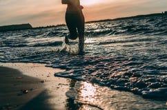 Девушка бежать на пляже на заходе солнца стоковое фото
