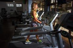 Девушка бежать на третбане в спортзале Стоковое Фото