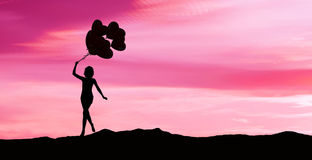 Девушка бежать с воздушными шарами на заходе солнца Стоковые Изображения