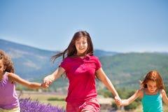 Девушка бежать с ее друзьями в поле лаванды Стоковое Изображение
