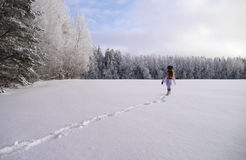 Девушка бежать через поле снега Стоковые Изображения