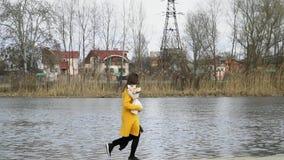 Девушка бежит в замедленном движении с букетом с розами вдоль пляжа реки, счастливого видеоматериал