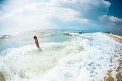 Девушка бежит далеко от волны стоковые изображения rf