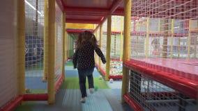 Девушка бежит через тоннель в лабиринте детей на спортивной площадке сток-видео