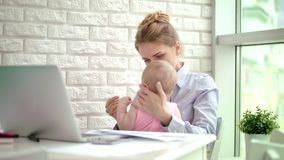 Девушка бизнес-леди обнимая в домашнем офисе Утомленный младенец в объятии матери сток-видео