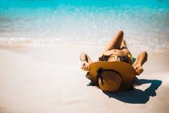 Девушка бикини держа шляпу и лежит вниз на пляже Стоковое Фото