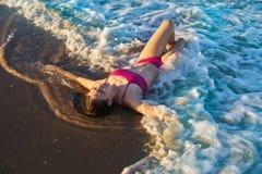Девушка бикини ослабила лежать на песке пляжа стоковые фотографии rf