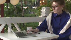 Девушка битника в стеклах выпивая кофе и писать в кафе лета акции видеоматериалы