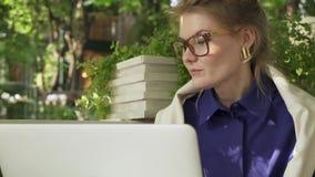 Девушка битника в стеклах выпивая кофе в кафе лета около ее компьтер-книжки видеоматериал