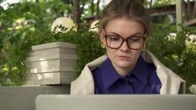Девушка битника в стеклах выпивая кофе в кафе около ее компьтер-книжки, съемке лета лотка акции видеоматериалы