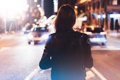 Девушка битника в черной кожаной куртке от задней части на свете в городе ночи атмосферическом, цене bokeh зарева освещенности фо Стоковое Изображение RF