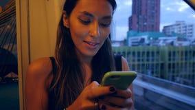 Девушка битника используя мобильный телефон в поезде Merto метро с окном города ночи на предпосылке 4K сток-видео