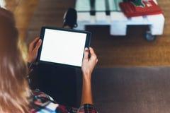 Девушка битника используя технологию таблетки в домашней атмосфере, персоне девушки держа компьютер с пустым экраном на bokeh пре Стоковое Изображение RF