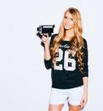 Девушка битника портрета блестящая с старым винтажным кино камера 8 mm снимая кино на белой предпосылке крыто цвет теплый стоковые фото