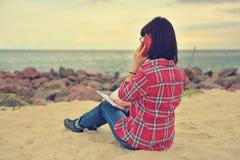 Девушка битника сидя с книгой и мобильным телефоном Стоковые Изображения RF