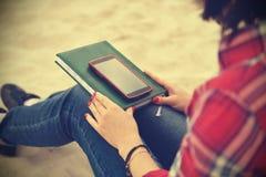 Девушка битника с книгой и мобильным телефоном Стоковое Изображение RF