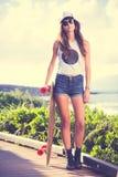 Девушка битника с солнечными очками доски конька нося Стоковое Изображение