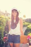 Девушка битника с солнечными очками доски конька нося Стоковые Фото