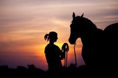 Девушка близко к лошади стоя перед красивым заходом солнца стоковая фотография rf
