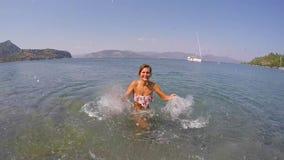 Девушка бросает воду к камере на море видеоматериал