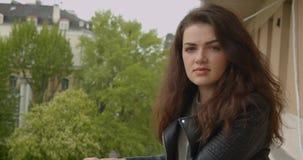 Девушка брюнета в кожаной куртке на балконе наслаждаясь впечатляющим видом на город наблюдает в камеру быть мечтательна и видеоматериал
