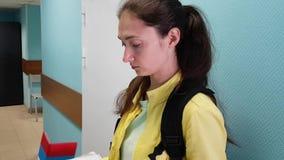 Девушка брюнета в комнате одного из заведений держа документы в ее руках, слегка ударяющ через бумагу видеоматериал