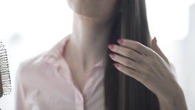 Девушка брюнета в розовой рубашке расчесывает ее красивый длинный гре сток-видео