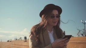 Девушка брюнета использует смартфон, сидя outdoors в солнечном дне, люди п сток-видео
