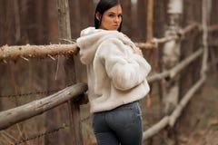 Девушка брюнета на деревянной загородке стоковое фото rf