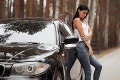Девушка брюнета положенная против автомобиля стоковые изображения